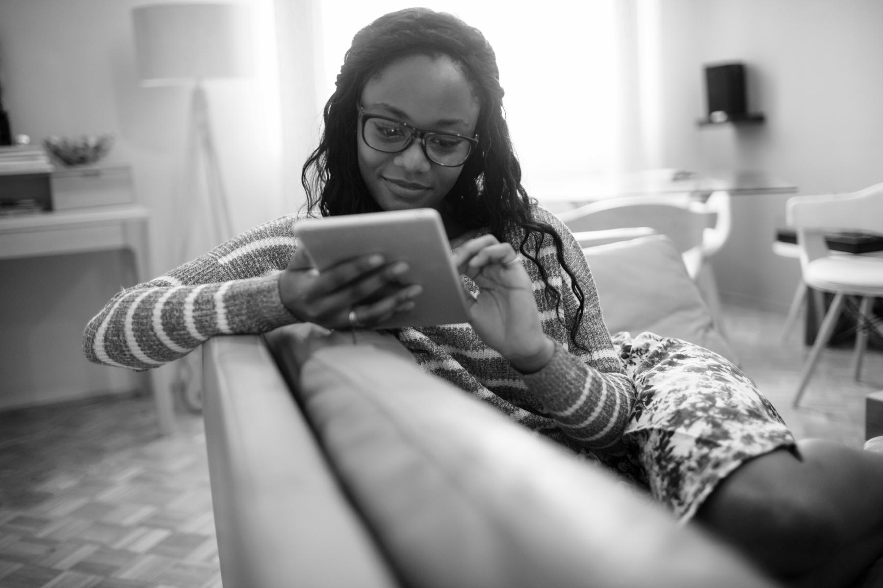 Photo of a young woman using her digital tablet while resting on the couch in her living room